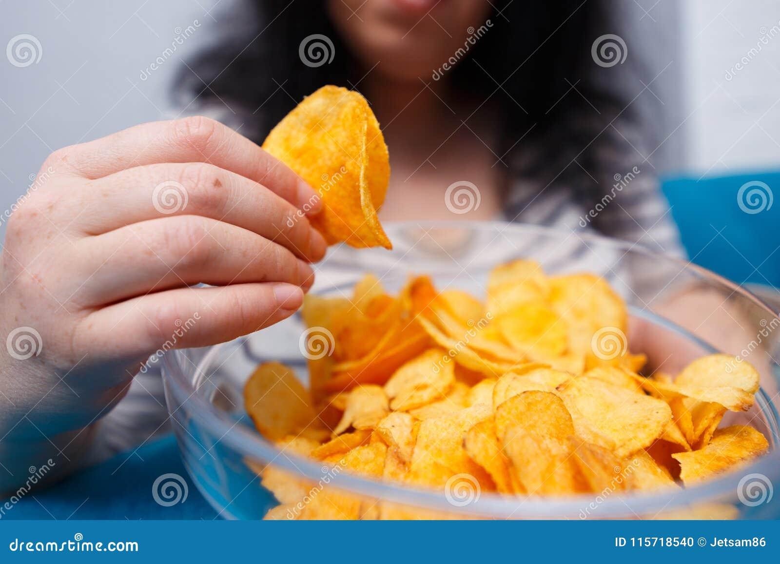 Vette vrouw die aan spaanders bereiken Het ongezonde eten, slechte gewoonten, voedsel