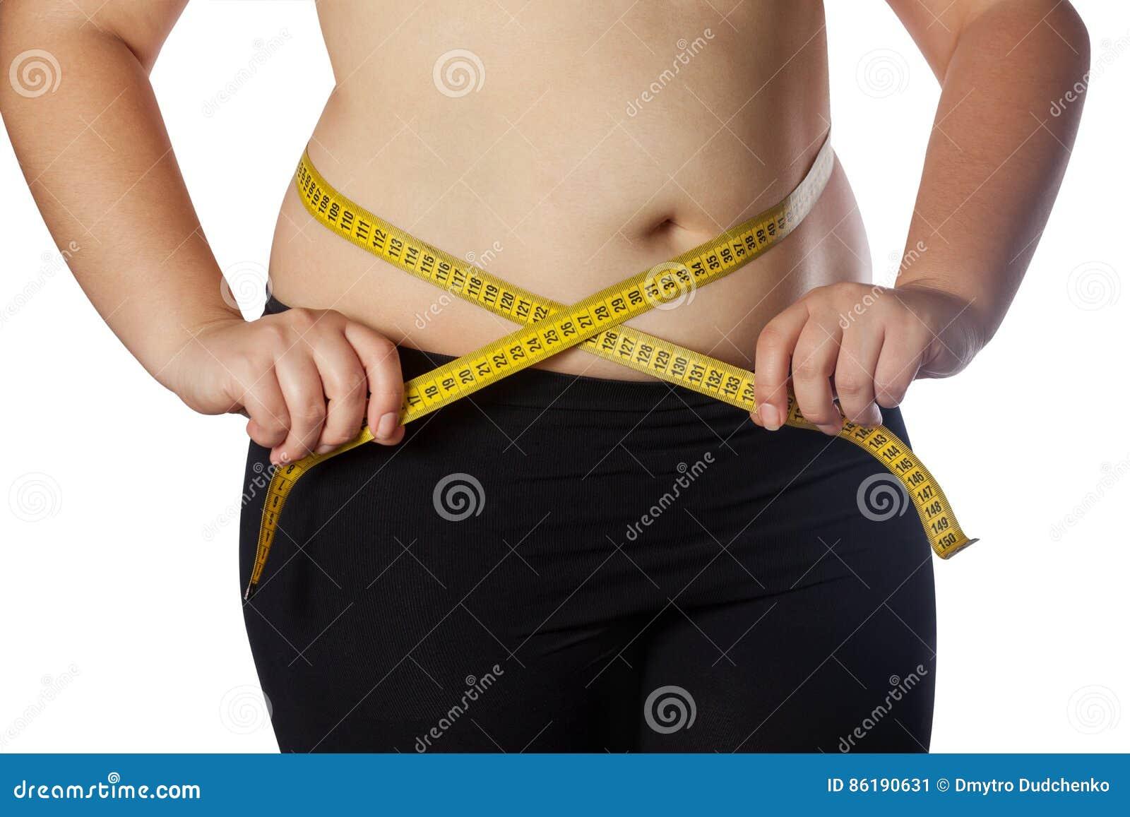 Vette vrouw die haar taille met een gele metende band meten Vermindering van overgewicht en zwaarlijvigheidsbehandeling