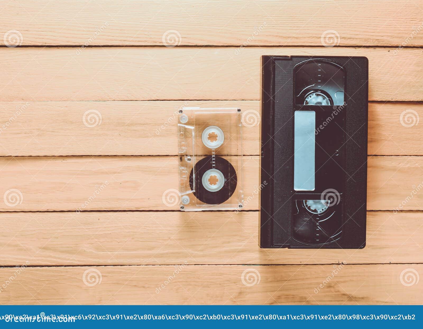 Vhs videocassette en audiocassette op een gele houten backgro