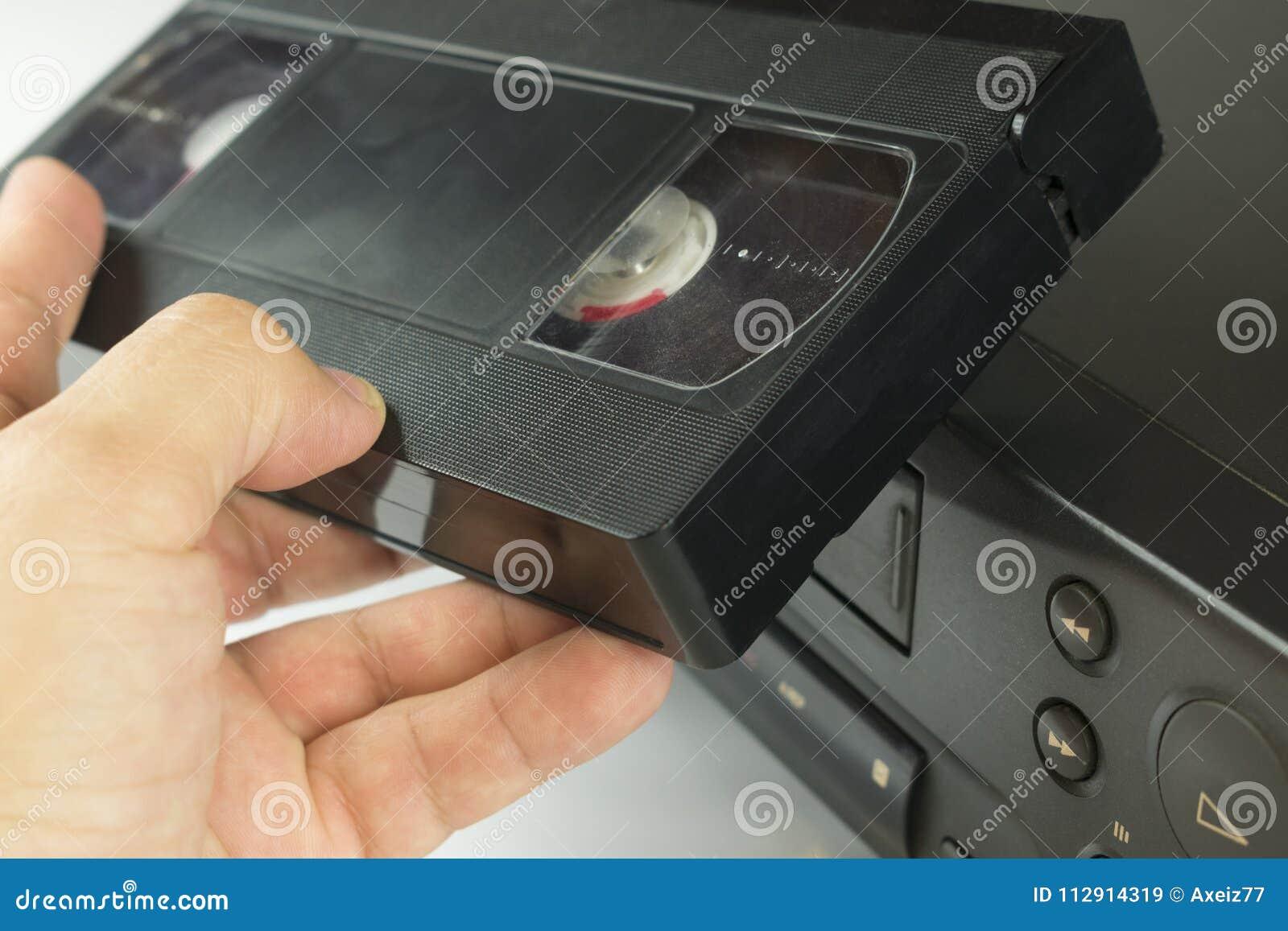 VHS videokassett i hand bredvid videobandspelare