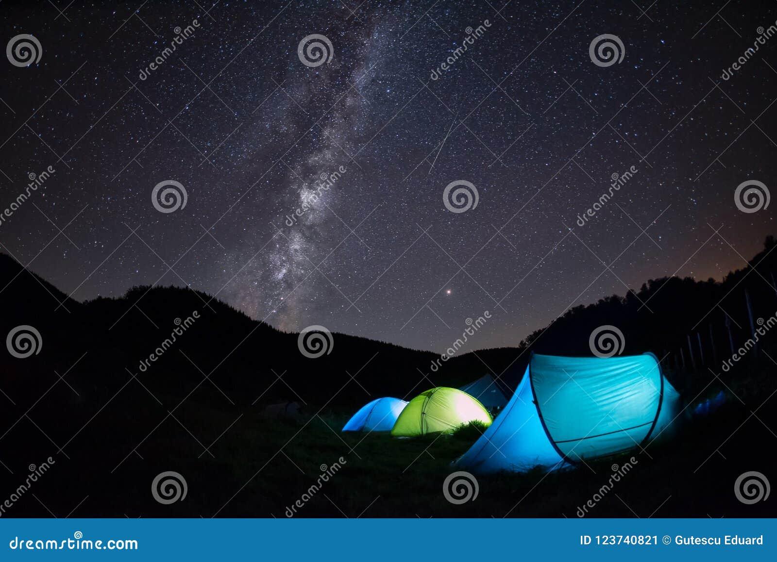 A Via Látea com as barracas que iluminam na noite, montanhas aventura-se no chuveiro de meteoro de Perseid