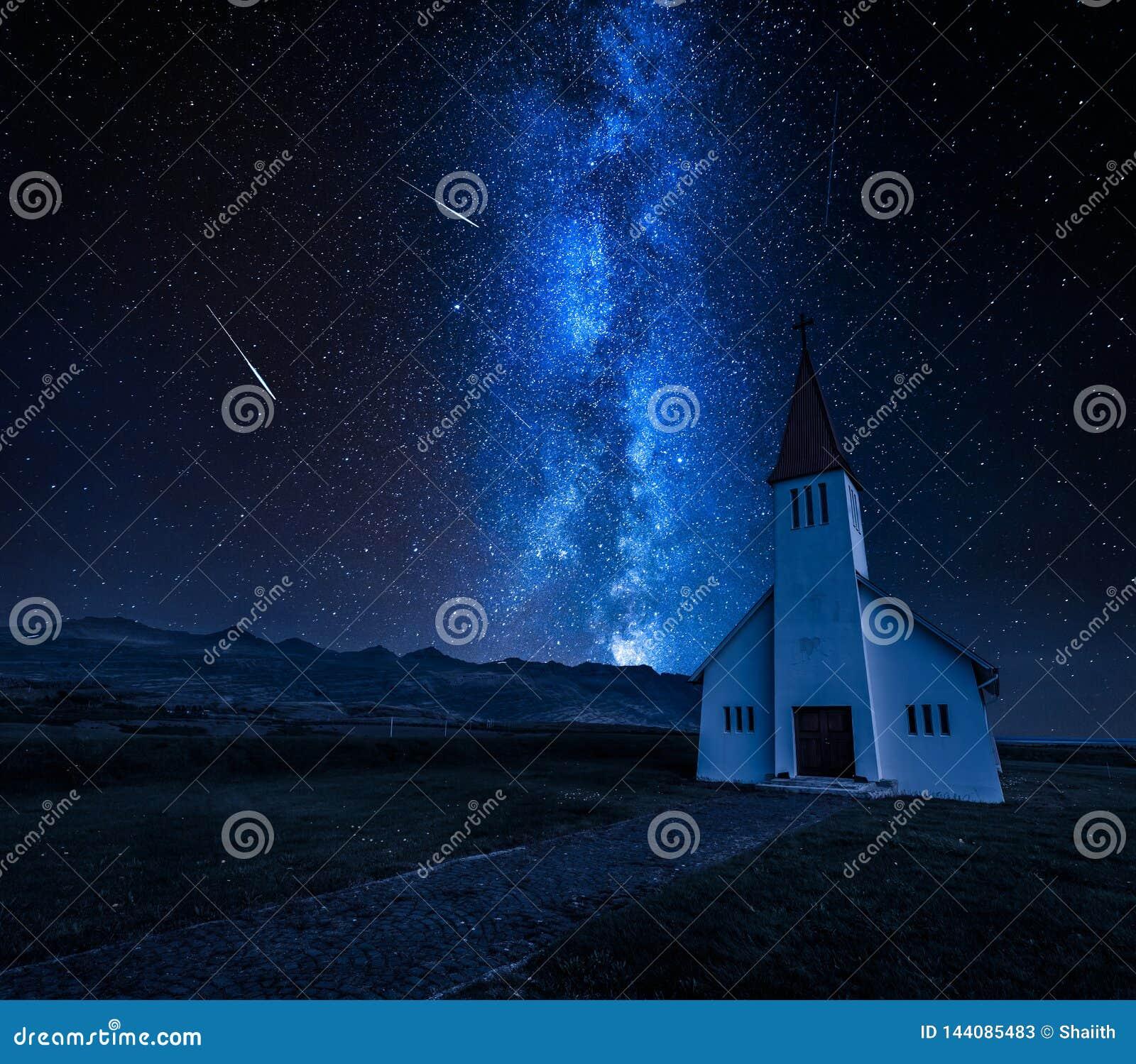 Via Látea sobre a igreja pequena na montanha, Islândia no verão