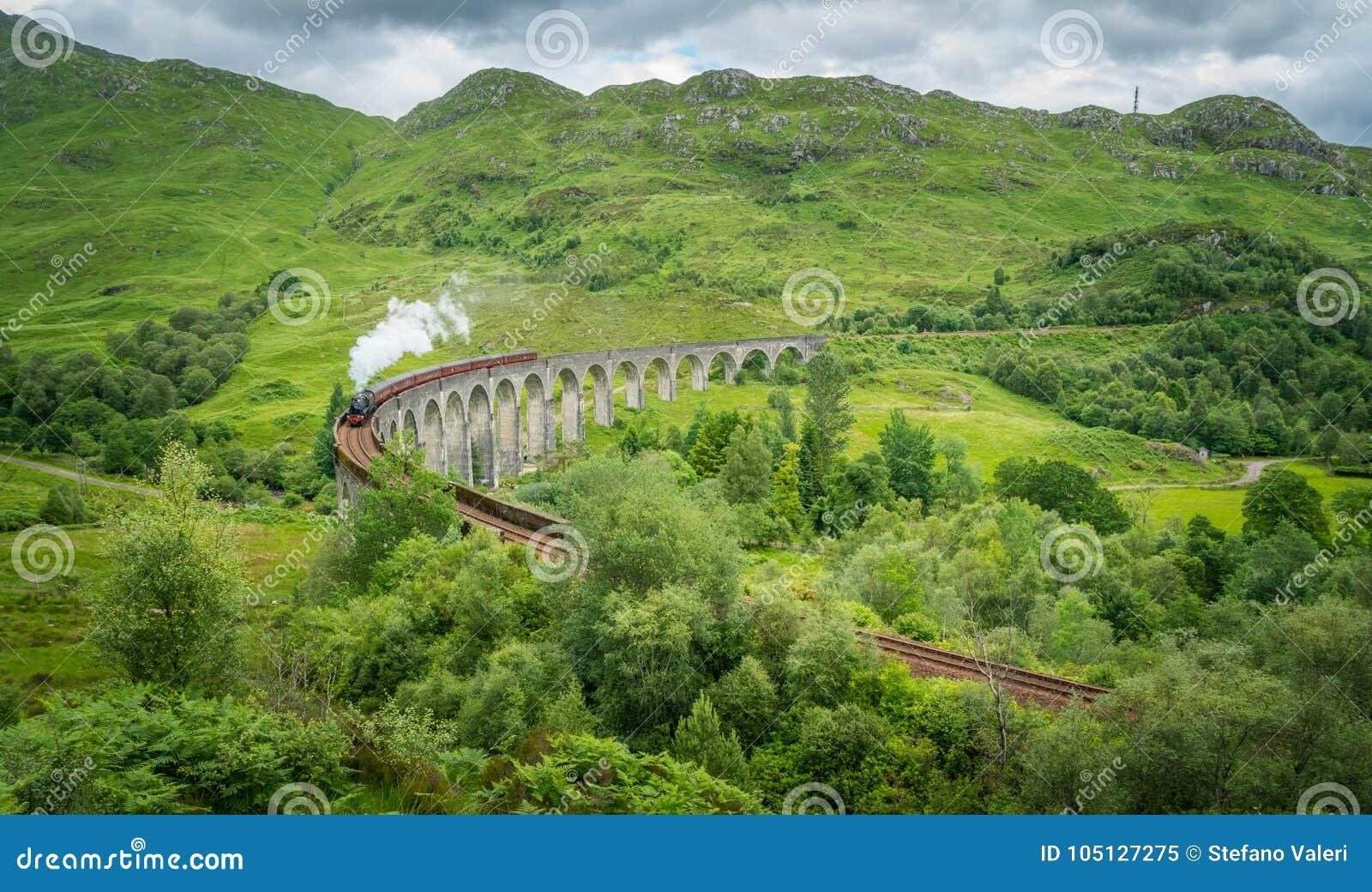 Viaduto Railway de Glenfinnan com o vapor de Jacobite, na área de Lochaber das montanhas de Escócia