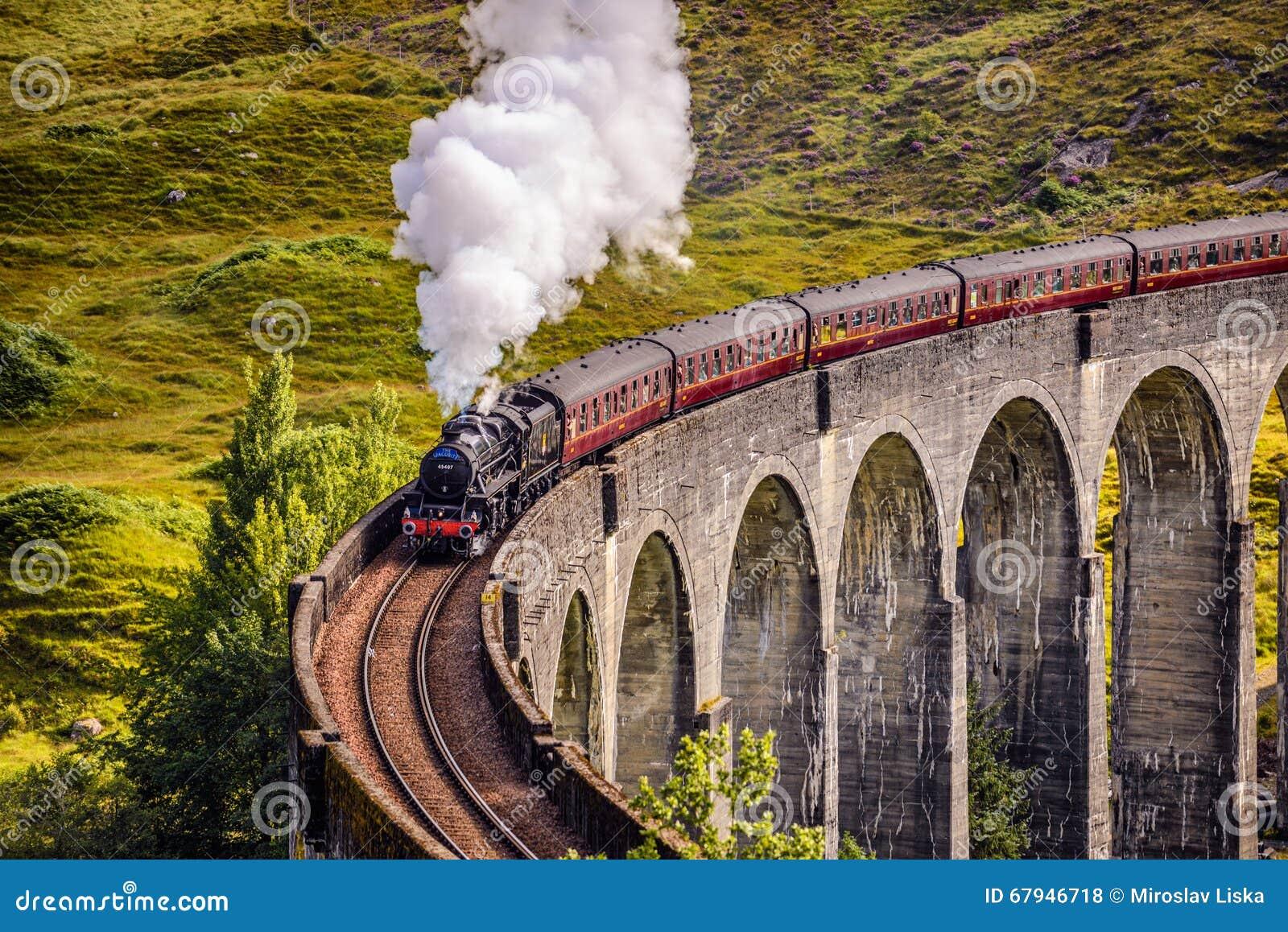 Viaduto Railway de Glenfinnan em Escócia com um trem do vapor