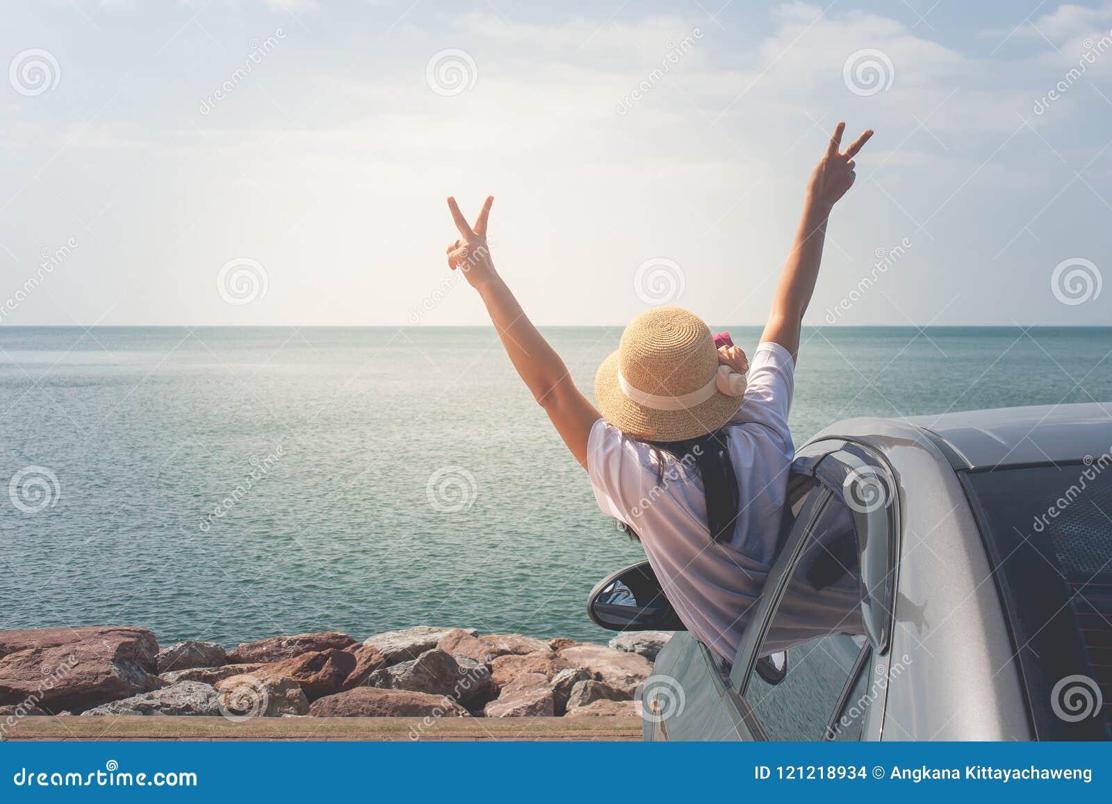 Viagem no mar, mulher do carro de família do retrato alegre levantando suas mãos acima e sentindo a felicidade