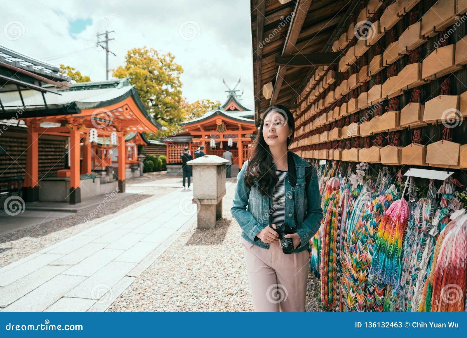 Viaggiatore asiatico della ragazza che cammina lungo la parete pregante