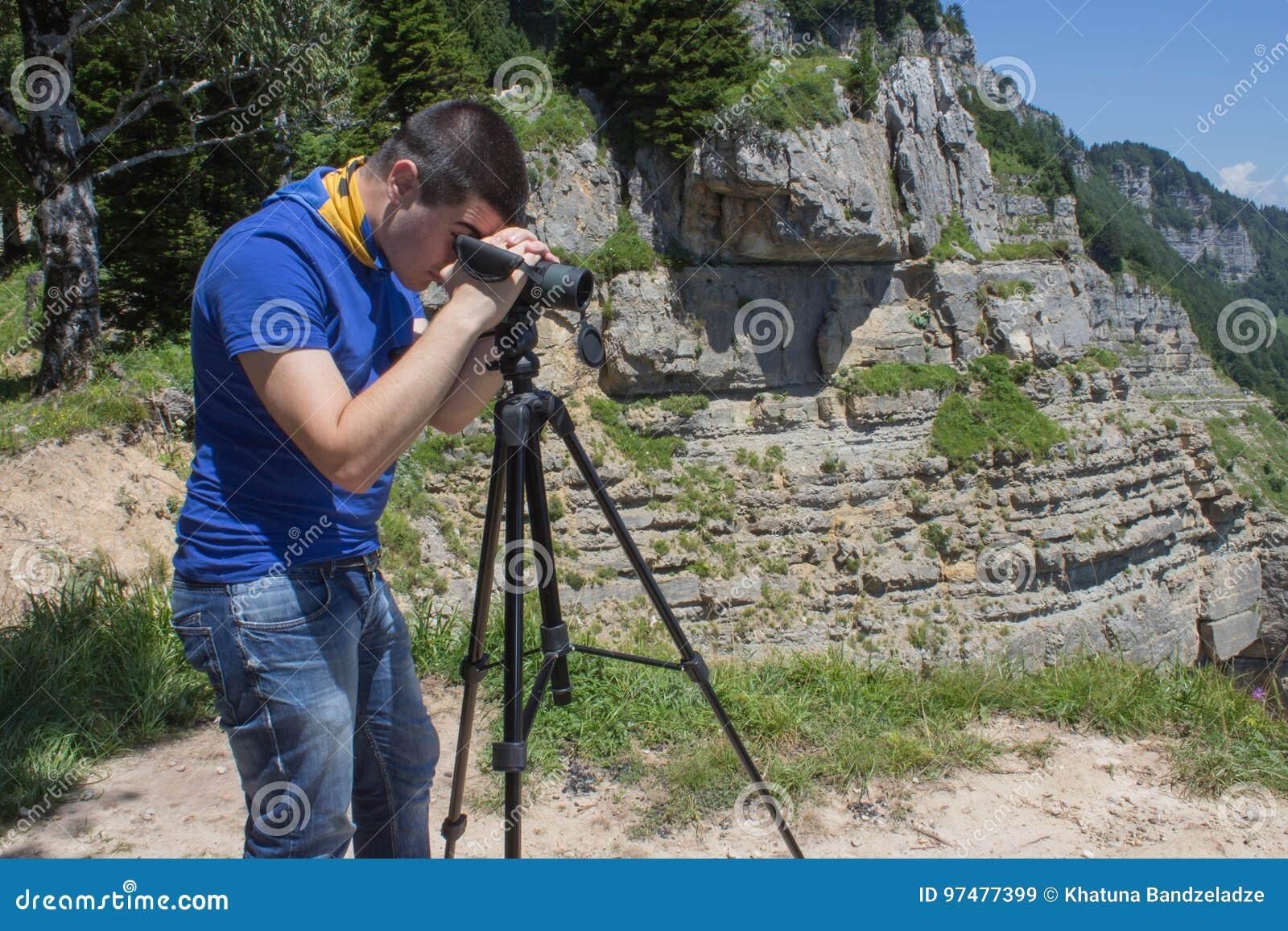 Viaggiatore che guarda la natura dall alta montagna con portata di macchia, treppiede del binocolo