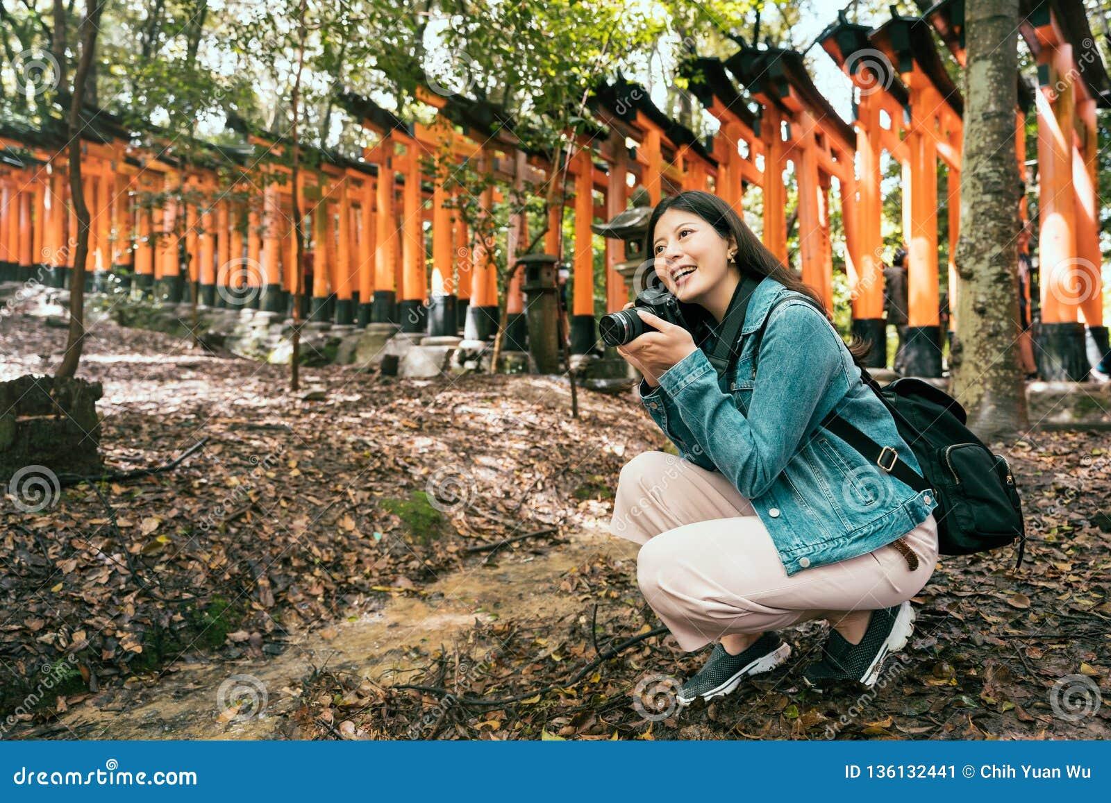 Viaggiatore con zaino e sacco a pelo in tempio che tiene macchina fotografica professionale