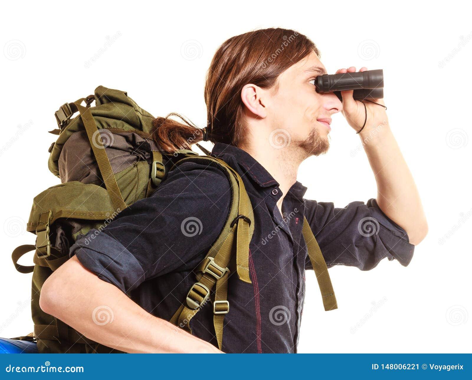 Viaggiatore con zaino e sacco a pelo turistico dell uomo che guarda tramite il binocolo