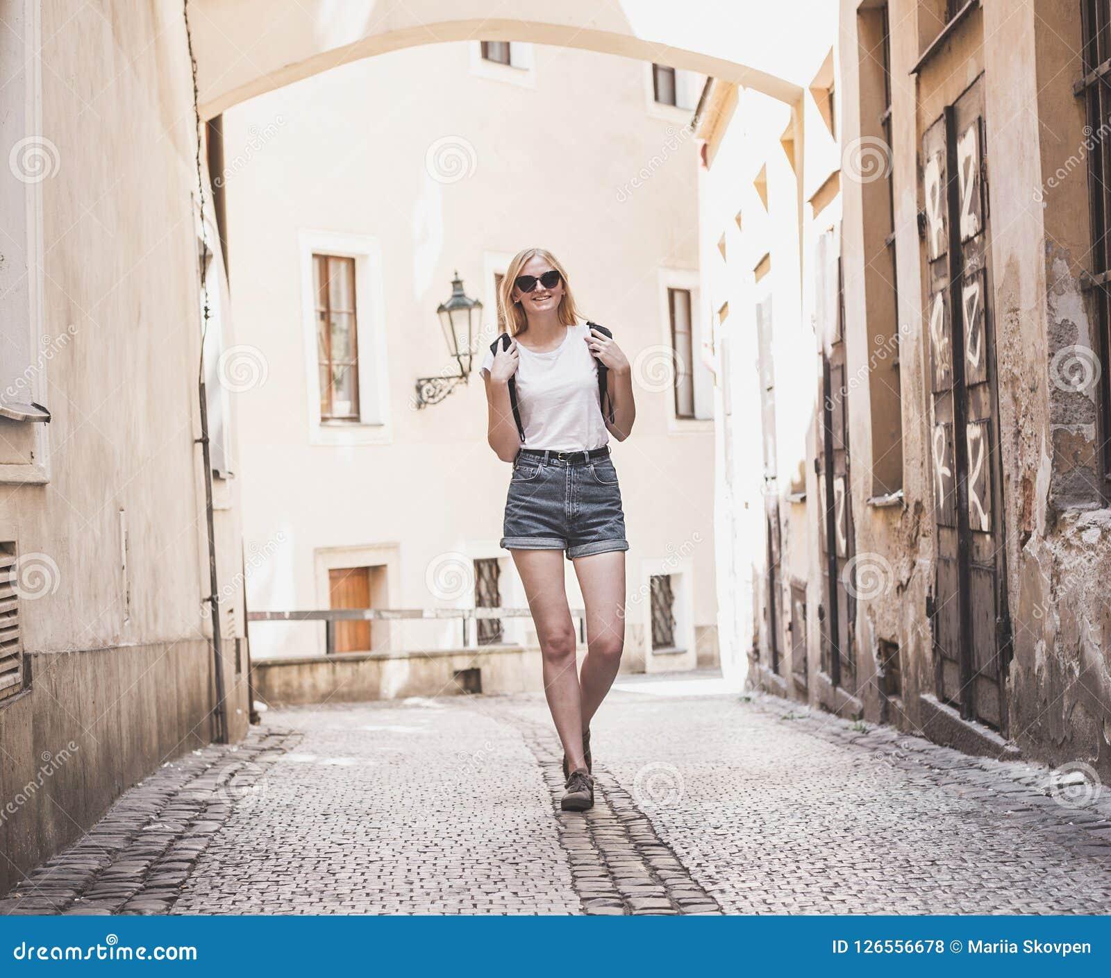 Viaggiatore della donna che cammina attraverso la galleria in città storica europea Ragazza dei pantaloni a vita bassa che viaggi