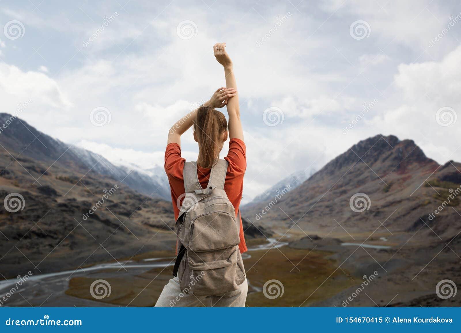 Viaggiatore della donna con uno zaino, ostacolante le sue mani, supporti sulla cima della montagna La bellezza della natura, mont
