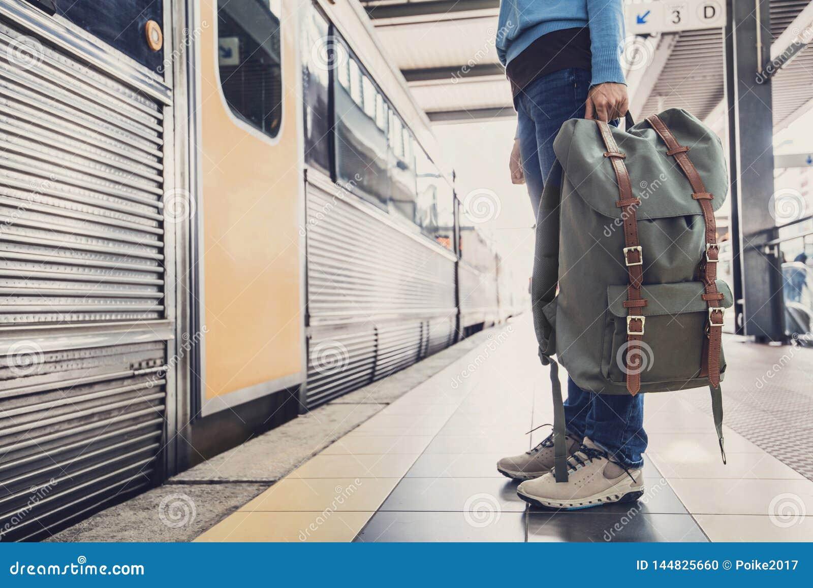 Viaggiatore della giovane donna che aspetta un treno su una stazione ferroviaria, su un viaggio e su un concetto attivo di stile