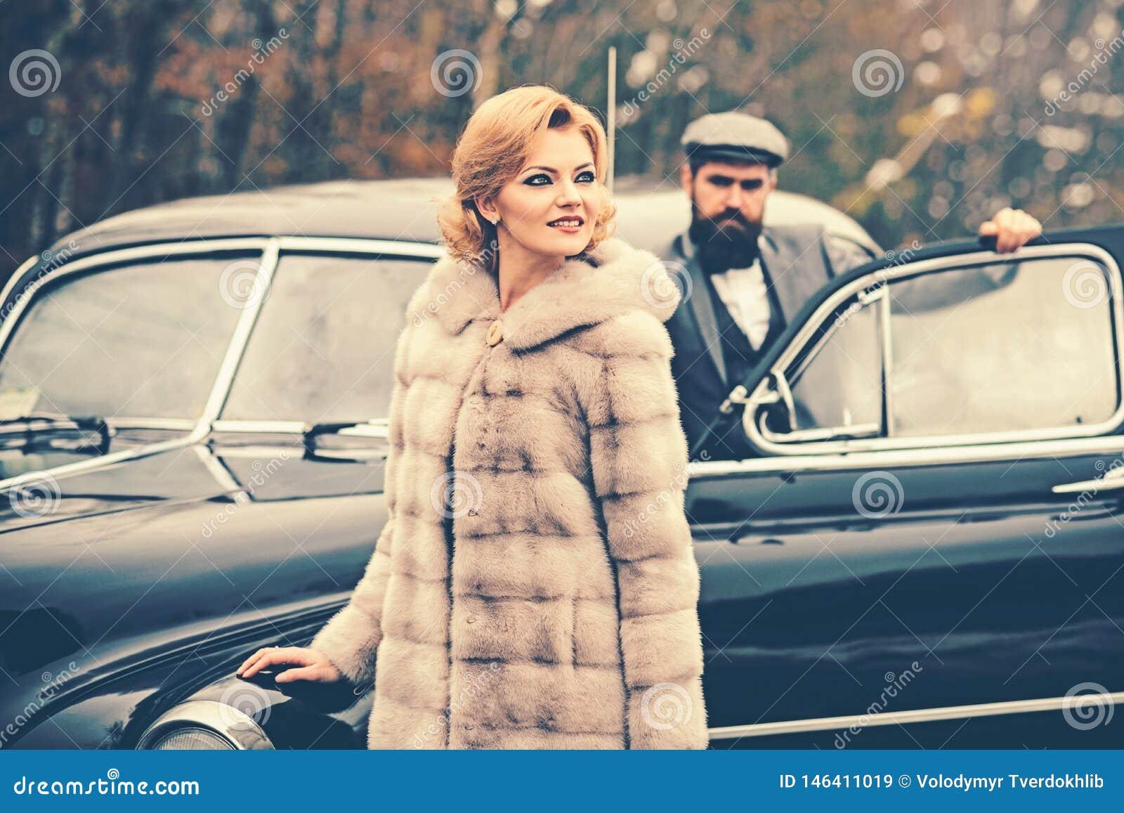 Viaggio e viaggio di affari o escursione del legamento Uomo barbuto e donna sexy in pelliccia Retro automobile della raccolta e r