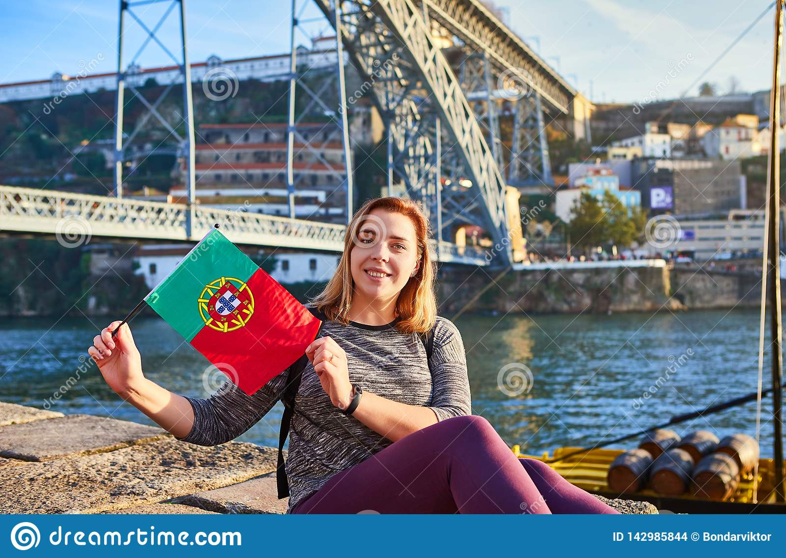 Viajante da jovem mulher que está para trás com a bandeira portuguesa, apreciando a opinião bonita da arquitetura da cidade no ri