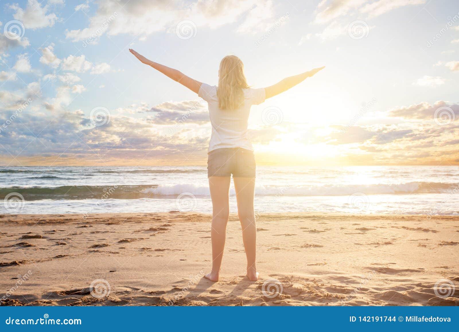 Viajante da menina em um alvorecer do sol da manhã em um resert tropical da praia A mulher bonita aprecia suas férias de verão, m