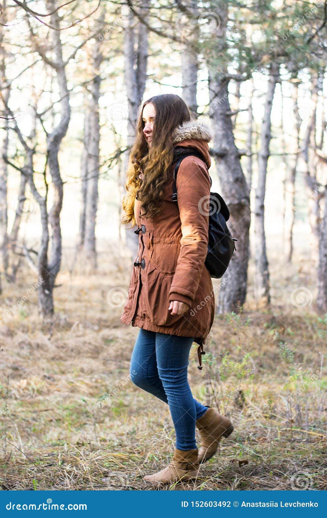 Viajante da mulher com a trouxa que olha a floresta de surpresa, conceito do curso do desejo por viajar, momento atmosférico