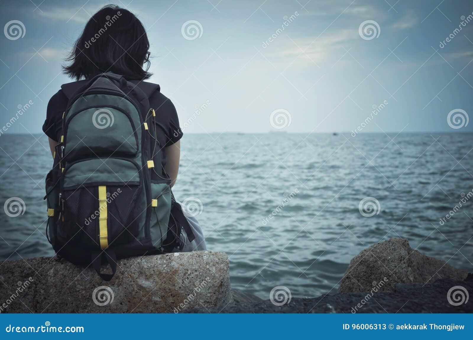 Viajante da mulher que senta-se na rocha para descansar