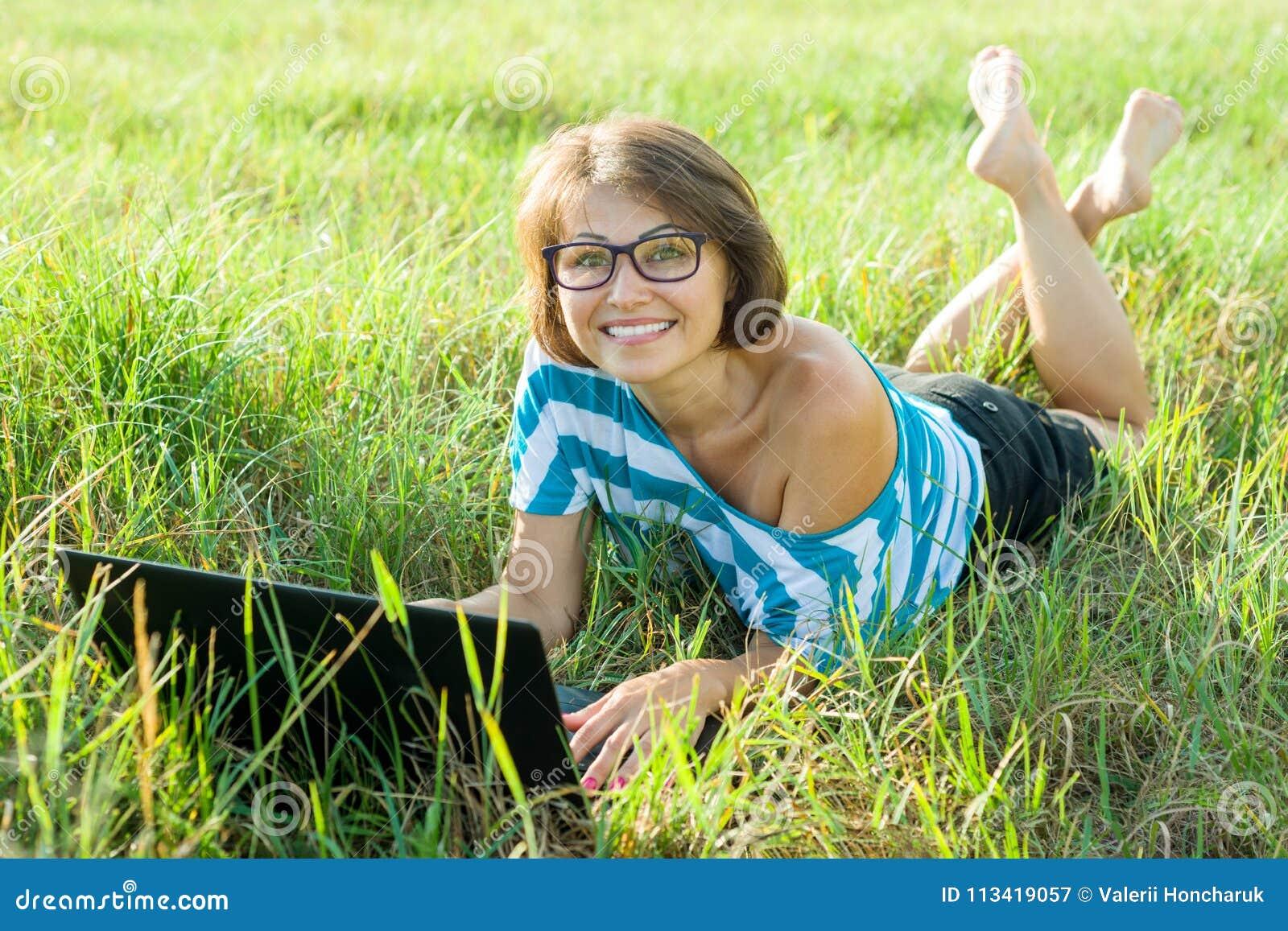 Viajante de meia idade de sorriso do blogger do freelancer da mulher do retrato exterior com o portátil na natureza