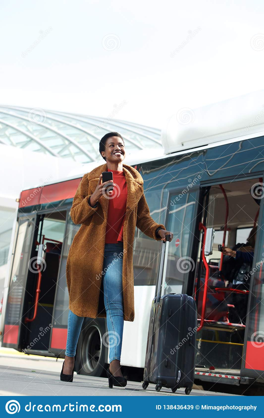 Viajante fêmea feliz do corpo completo que anda pelo ônibus com saco e telefone celular da mala de viagem