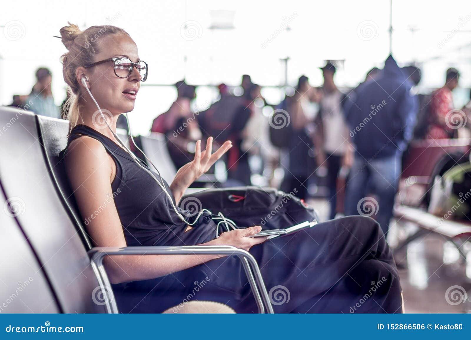 Viajante f?mea que fala no telefone celular ao esperar para embarcar um plano em portas de partida no terminal de aeroporto asi?t