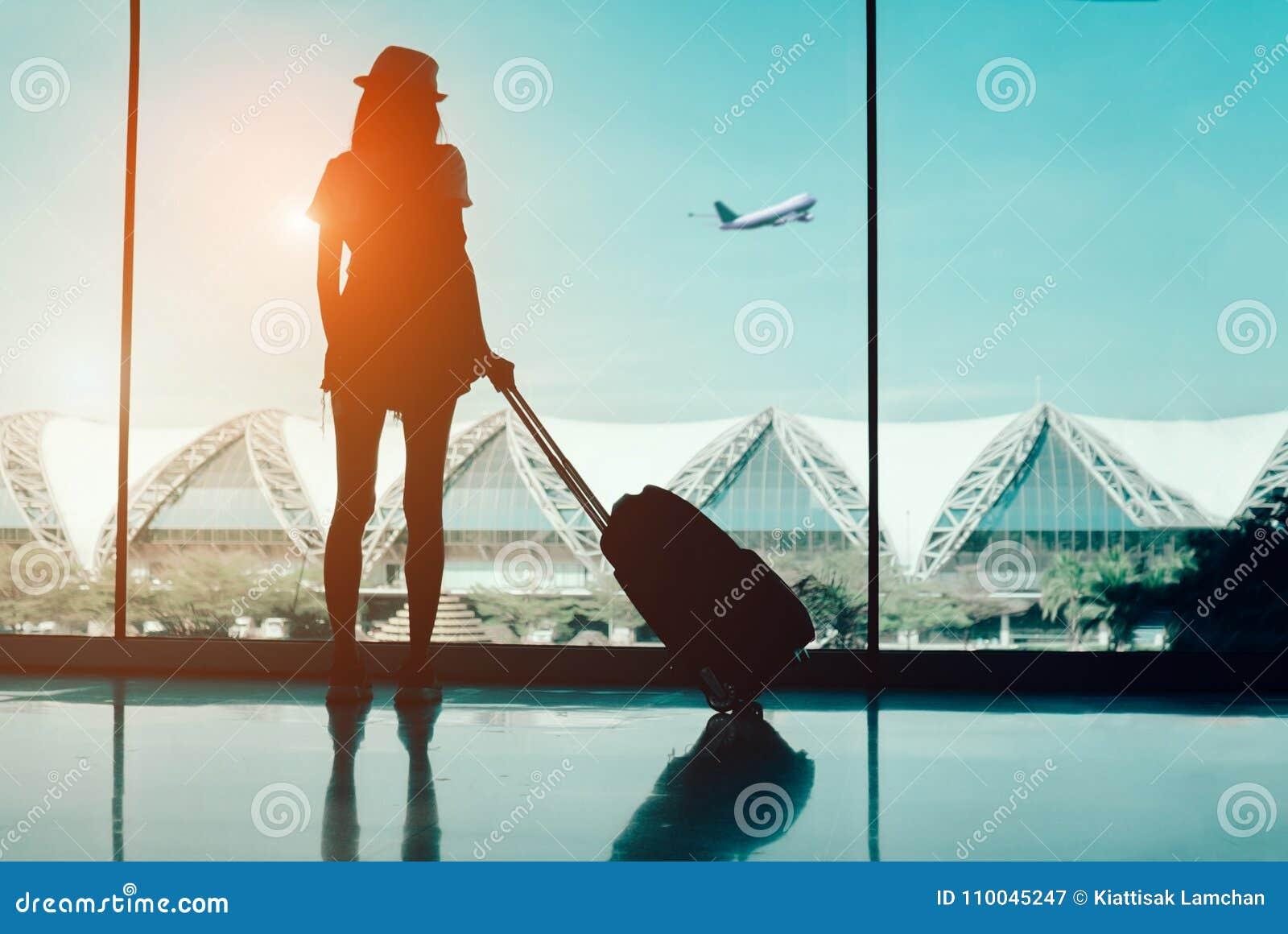 Viaje de la mujer de la silueta con el equipaje que mira sin la ventana el international del terminal de aeropuerto o el adolesce