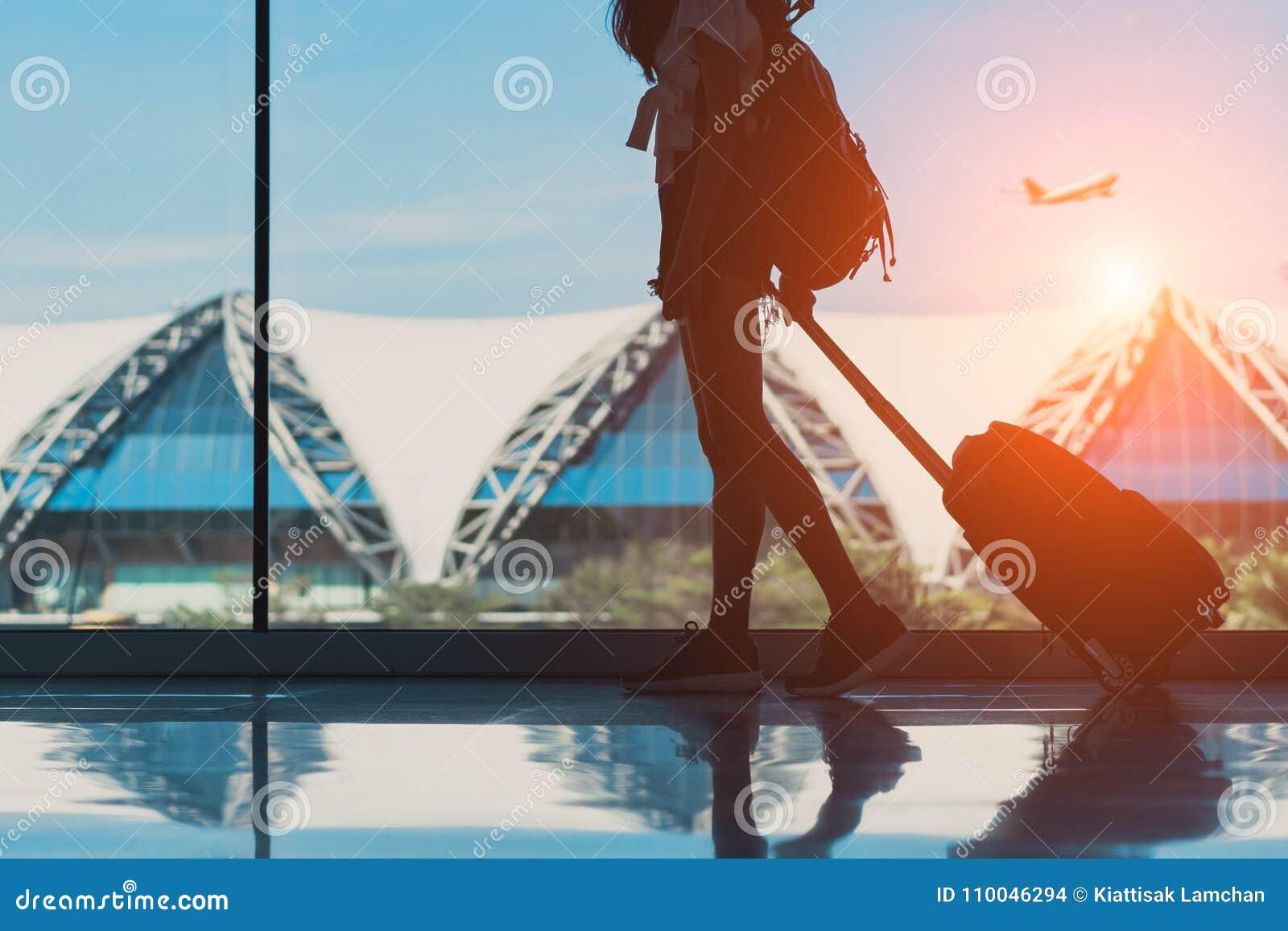 Viaje de la mujer de la silueta con la ventana lateral que camina del equipaje en el international del terminal de aeropuerto
