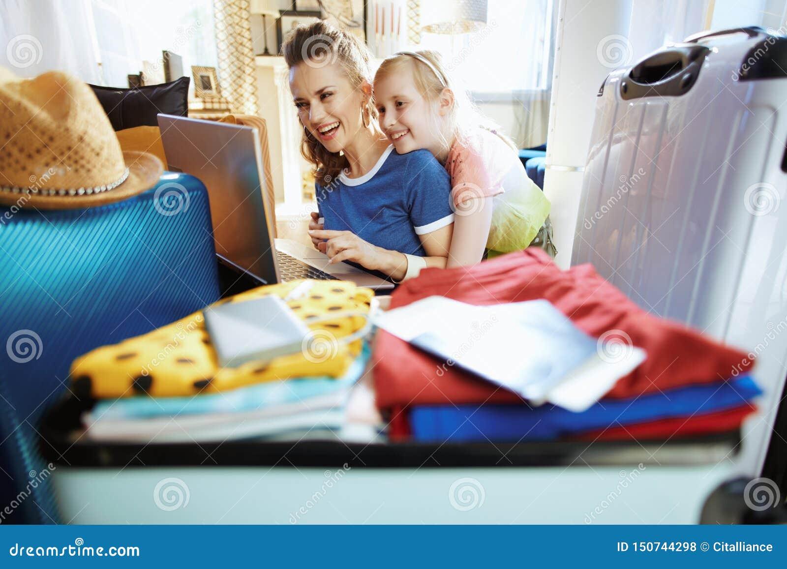 Viaje moderno sonriente del planeamiento de la madre y del niño en línea