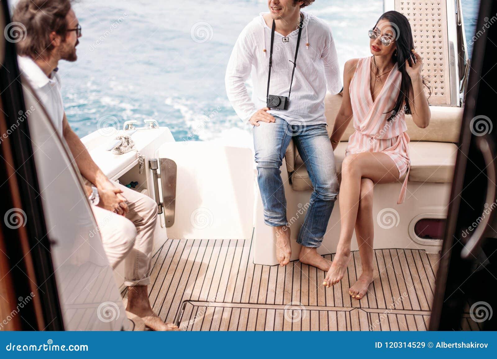 Viaje, seatrip, amistad y concepto de la gente - amigos que se sientan en cubierta del yate