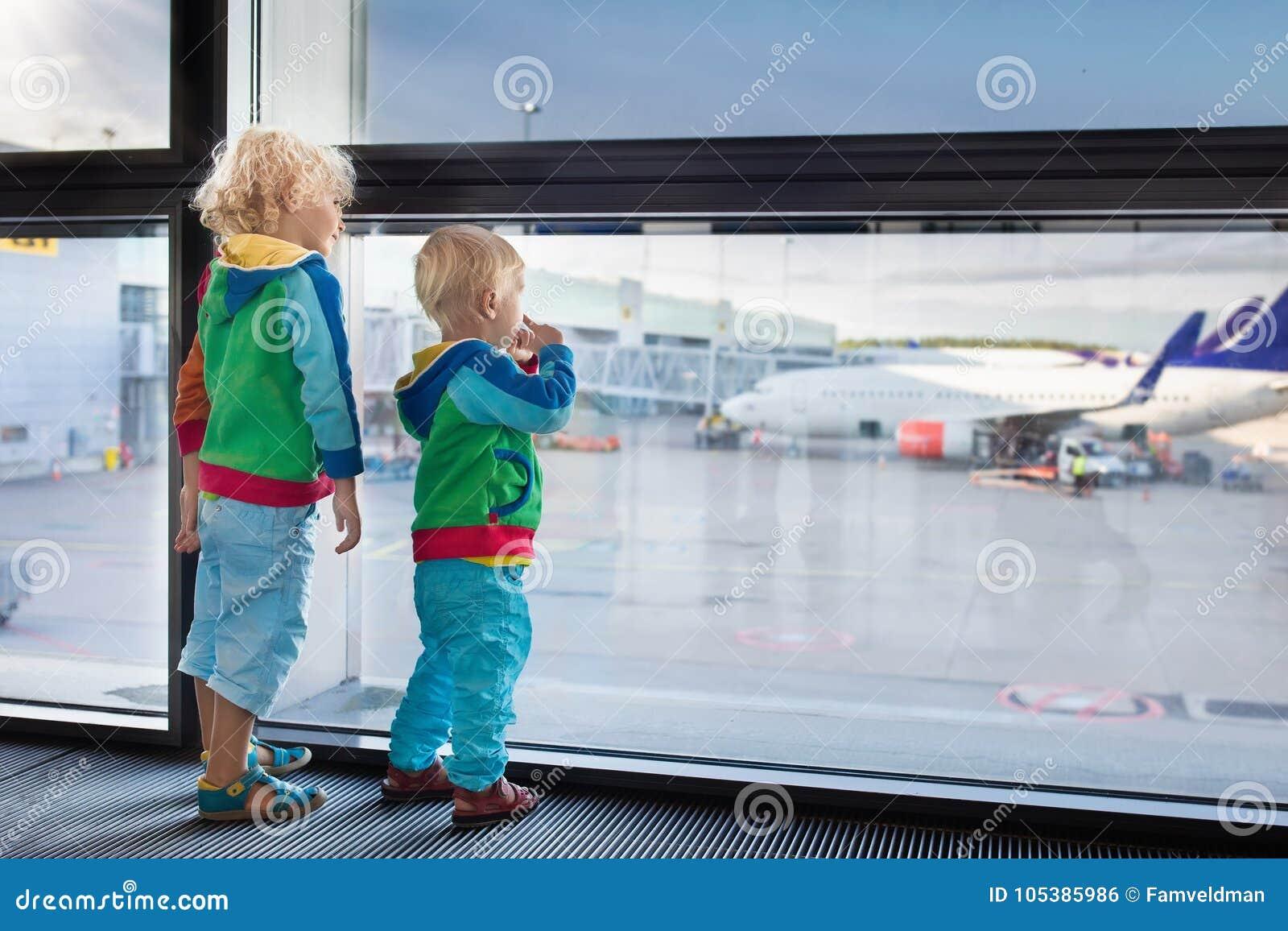 Viaje y mosca de los niños Niño en el aeroplano en aeropuerto