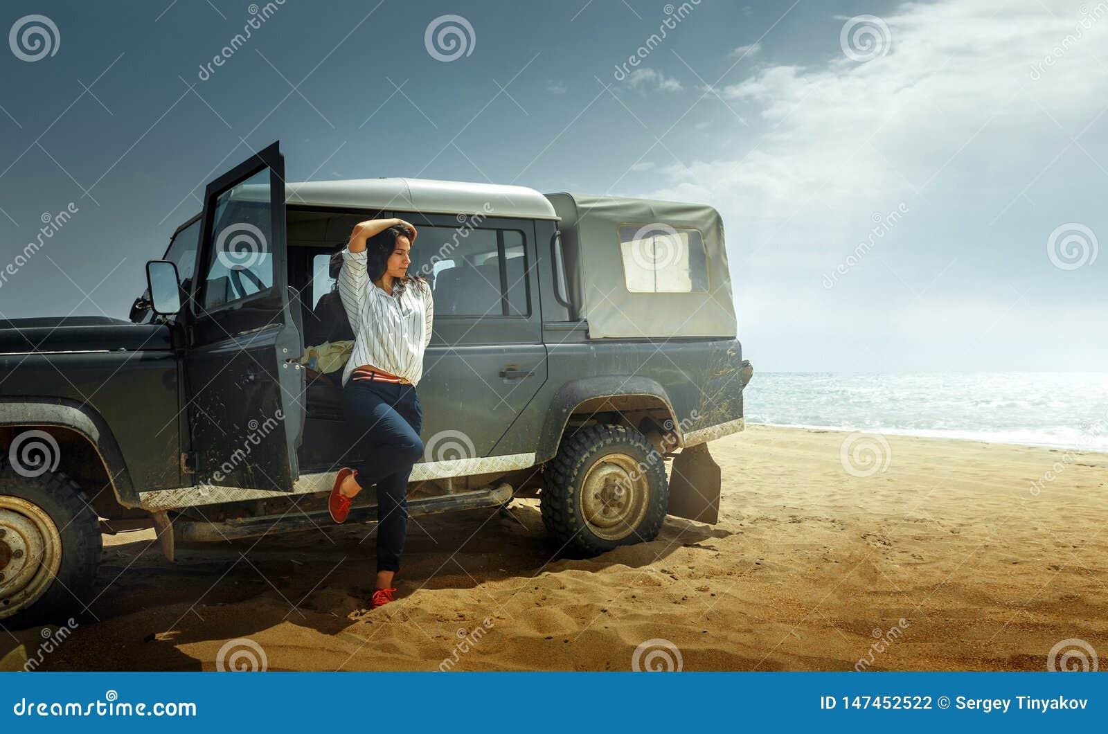 Viajero atractivo de la mujer joven que disfruta de la opinión del mar, inclinándose detrás en un coche clásico SUV