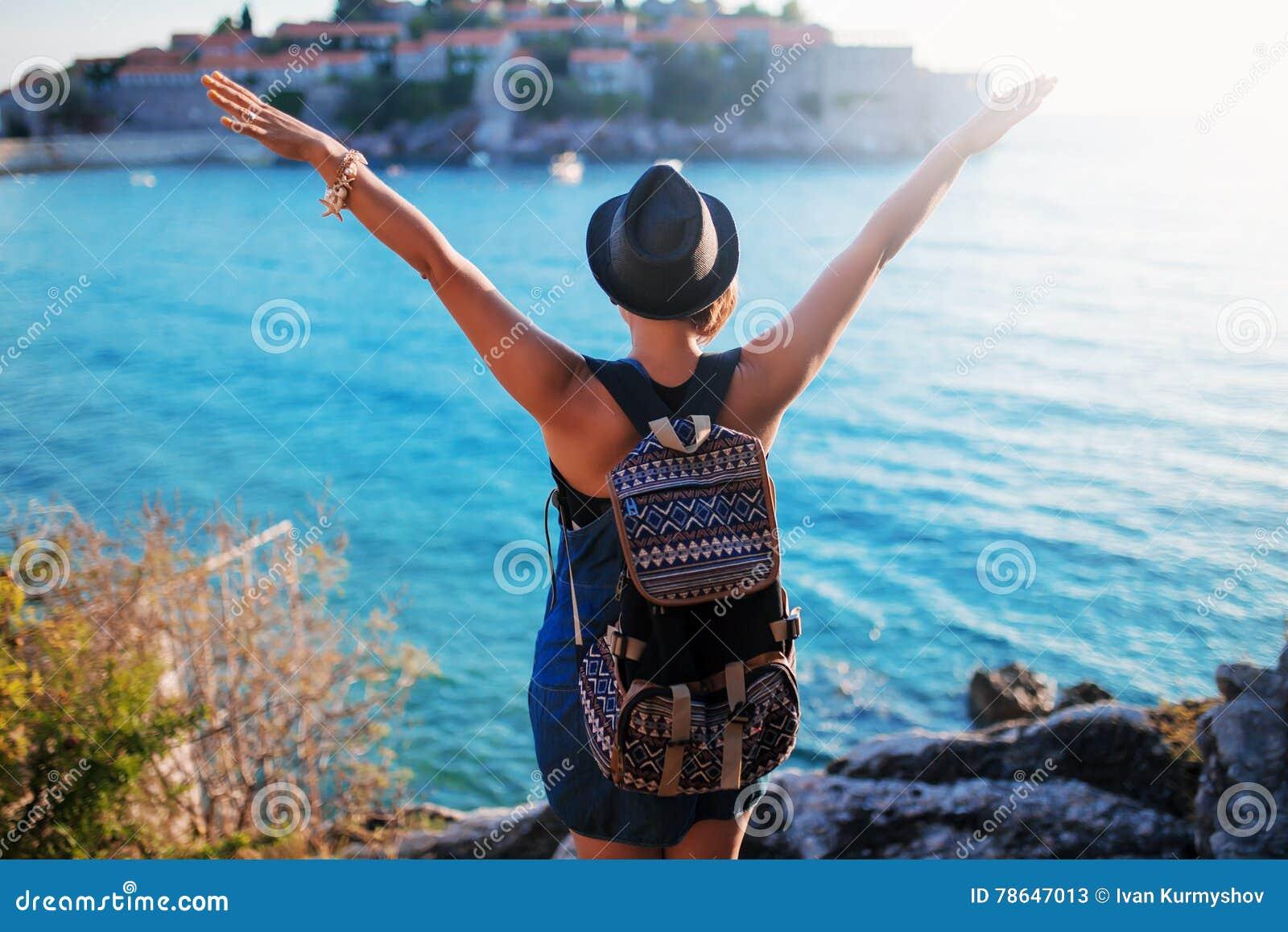 Viajero de la mujer con la mochila cerca de Sveti Stefan en el mar adriático