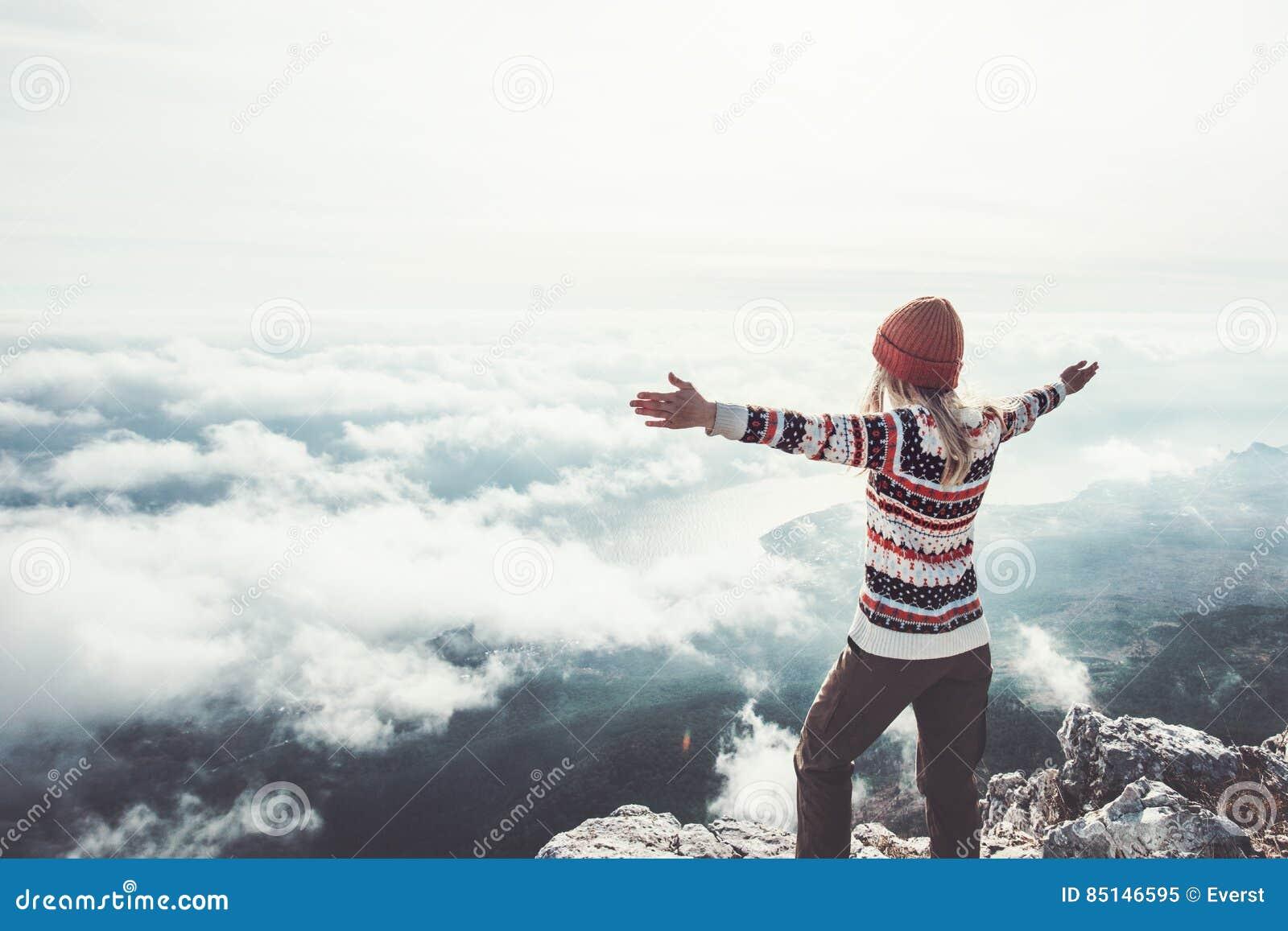 Viajero feliz de la mujer en las manos de la cumbre de la montaña aumentadas