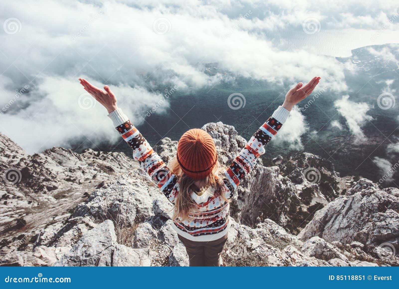 Viajero feliz de la mujer en las manos de la cumbre de la montaña aumentadas para arriba