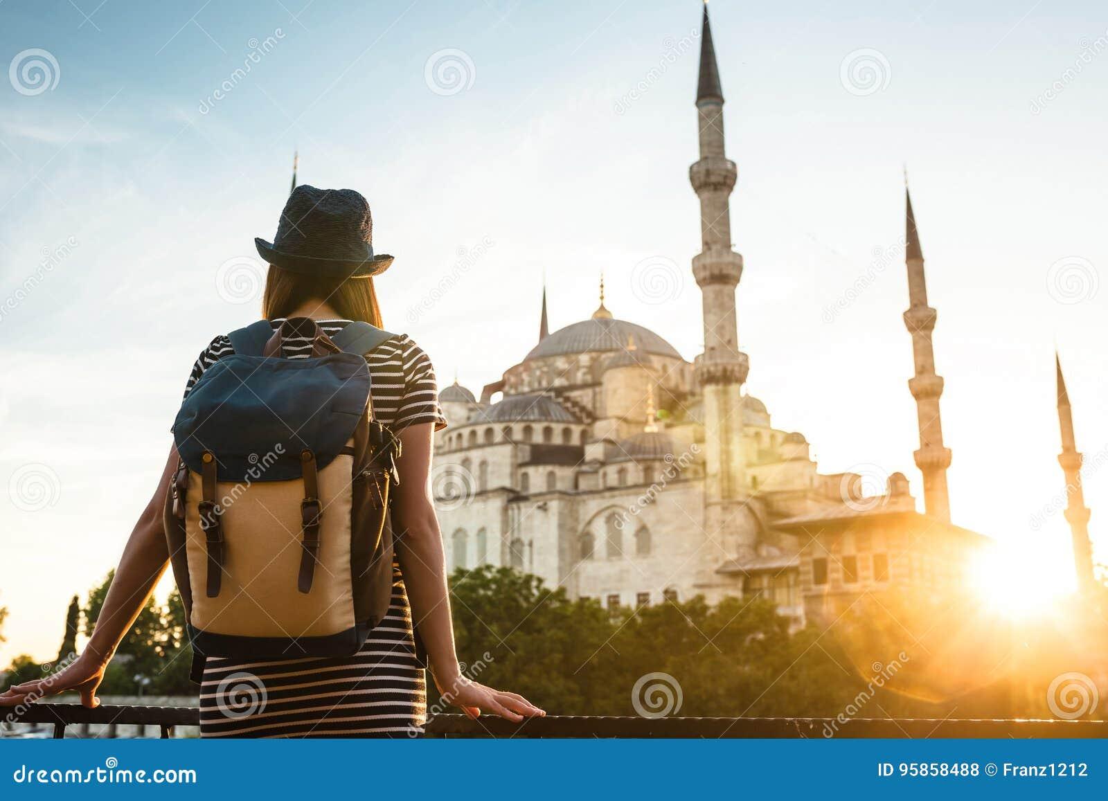 Viajero hermoso joven de la muchacha en un sombrero con una mochila que mira una mezquita azul - una atracción turística famosa d