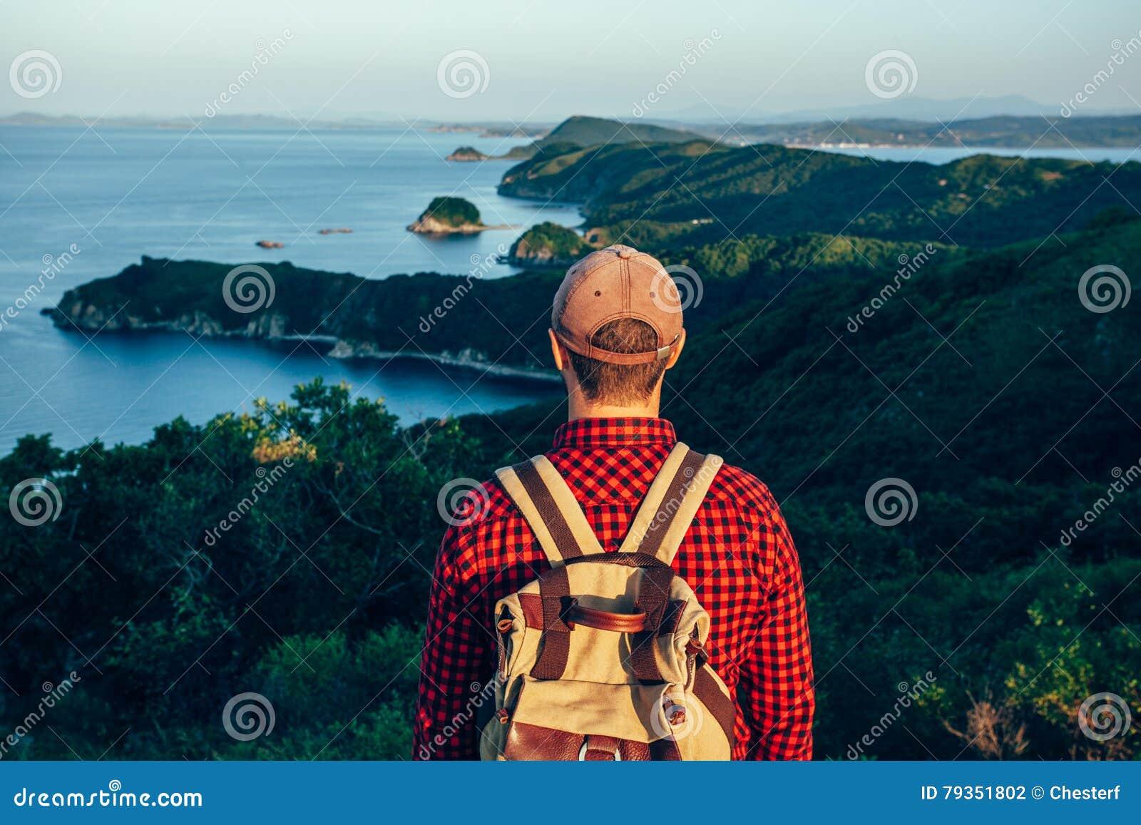 Viajero masculino de la parte posterior en la costa de mar