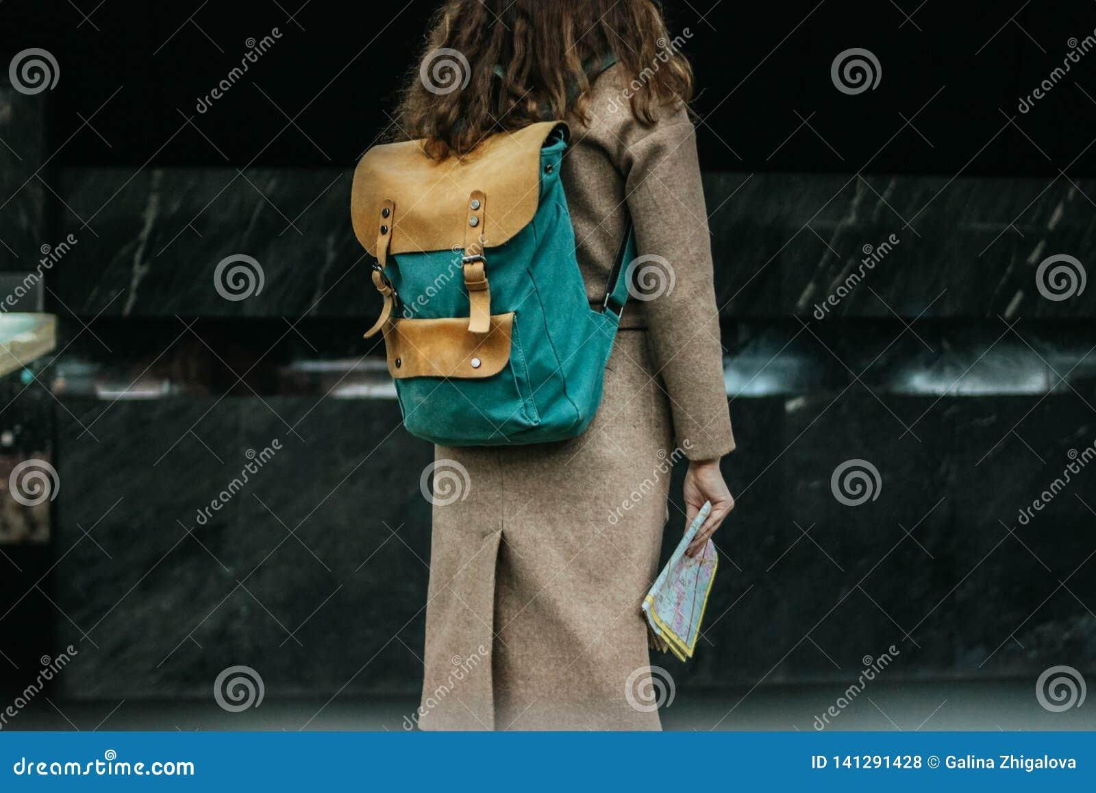 Viajero principal rojo rizado de la muchacha de la mujer joven con la mochila y mapa en la estación de metro