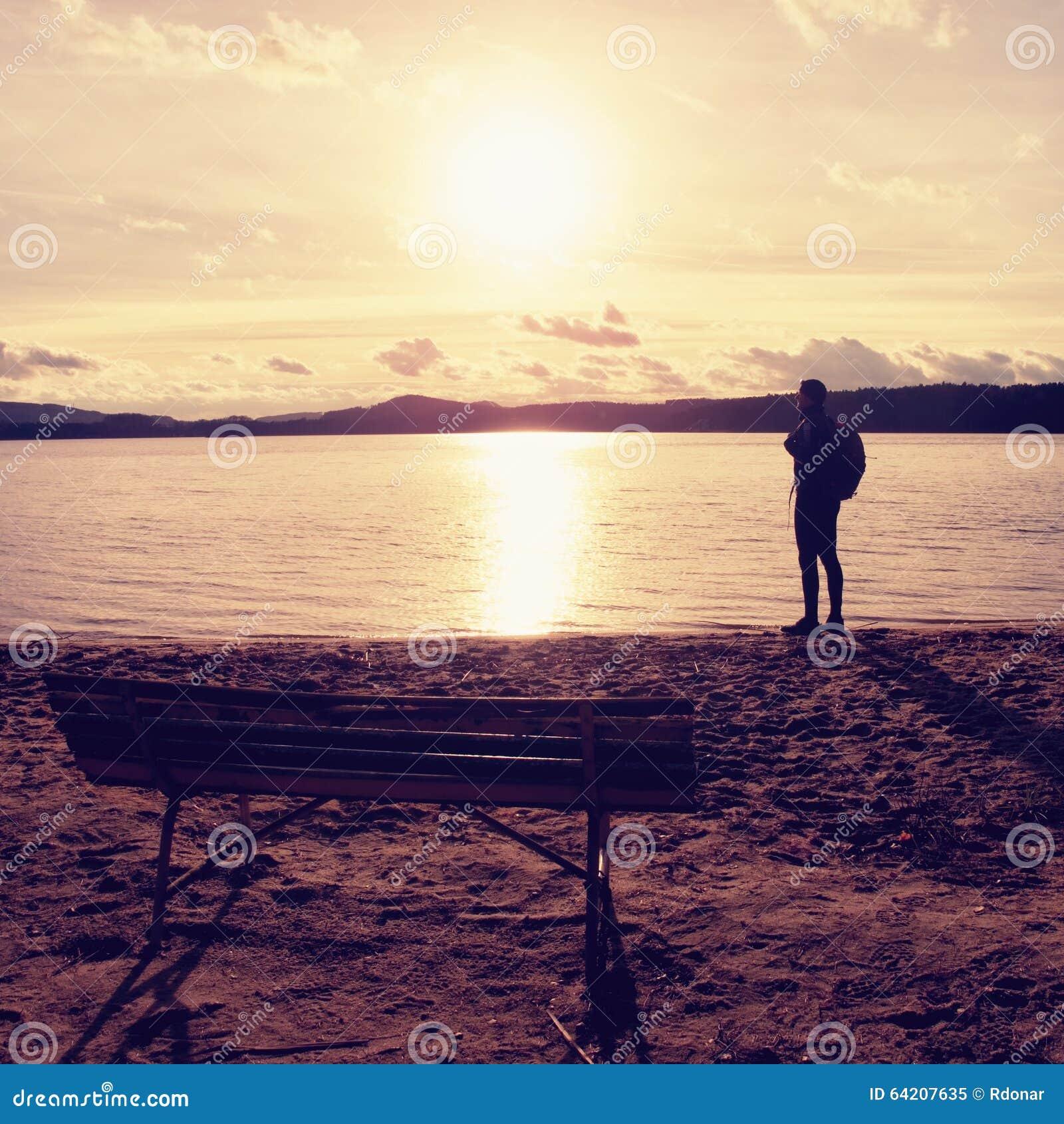 Viajero solo con la mochila Hombre en la playa del mar en el banco de madera, tarde soleada fría del otoño
