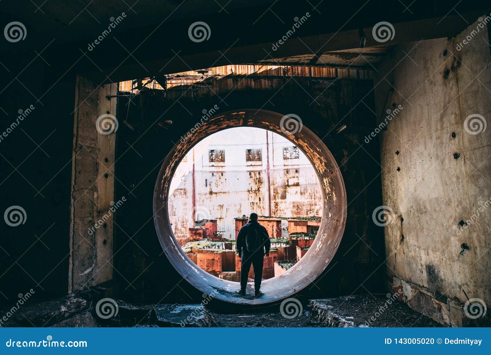 Viajero y explorador dentro de la puerta redonda o puerta del hombre al sitio nuclear abandonado del rector o del generador en NP