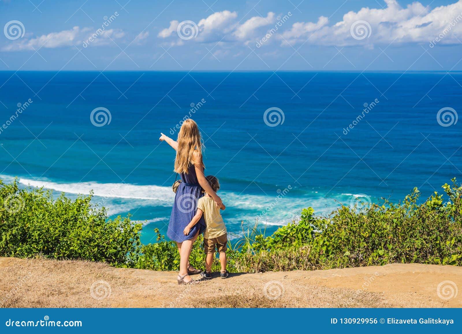 Viajeros de la mamá y del hijo en un acantilado sobre la playa Paraíso vacío