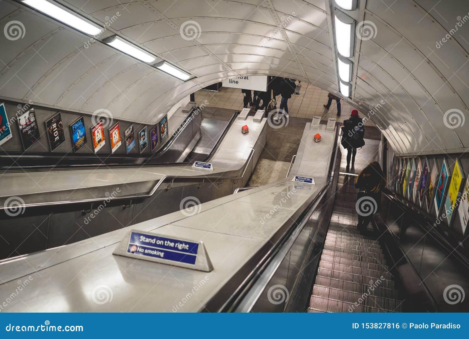 Viajeros en una escalera móvil en una estación del metro en Londres Reino Unido En junio de 2017