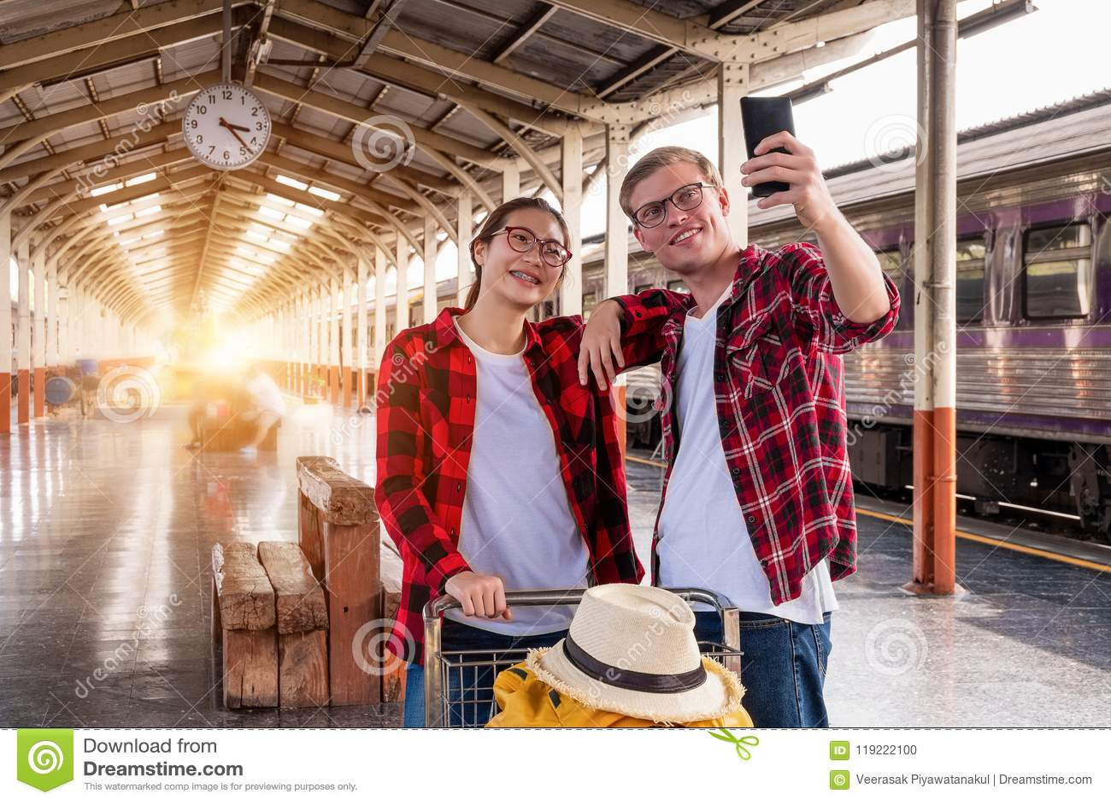 Viajeros jovenes felicesdel couplejunto de vacaciones que toman un selfie en el teléfono en la estación de tren, concepto del