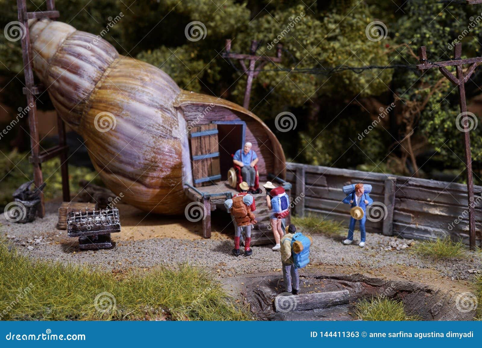 Viajeros miniatura que se colocan en la casa del caracol