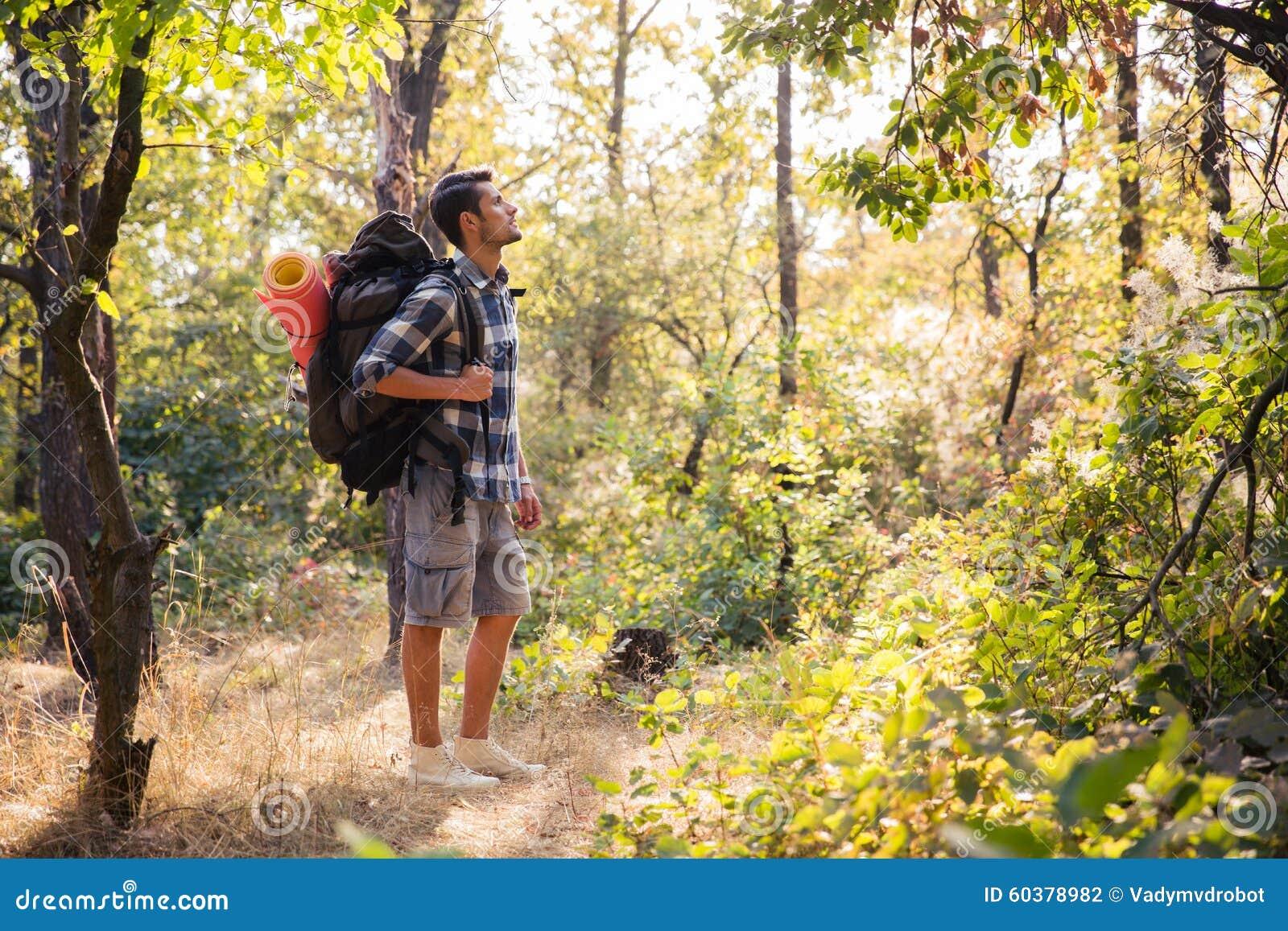 Viandante maschio che cammina nella foresta