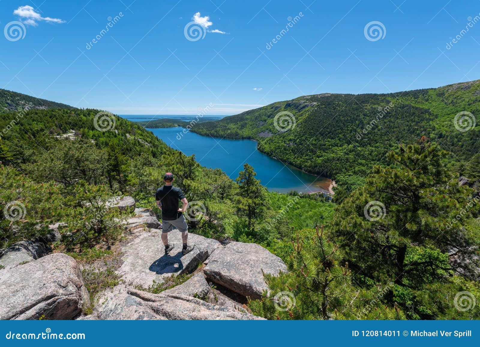 Viandante maschio che gode del punto di vista di Jordan Pond nel parco nazionale di acadia