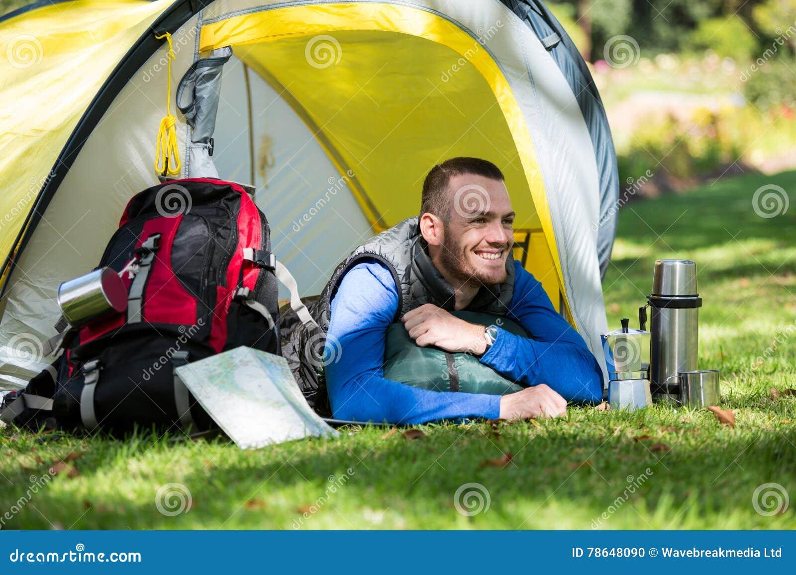 viandante sorridente che si trova in tenda fotografia