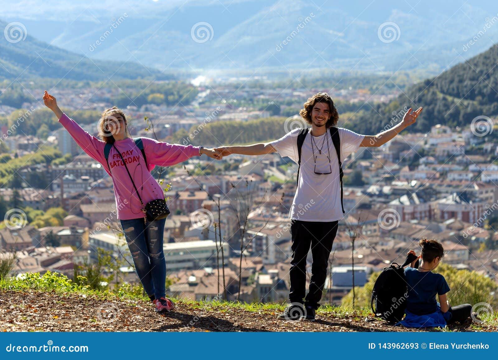 Viandanti con gli zainhi che si rilassano sopra una montagna e che godono della vista della valle