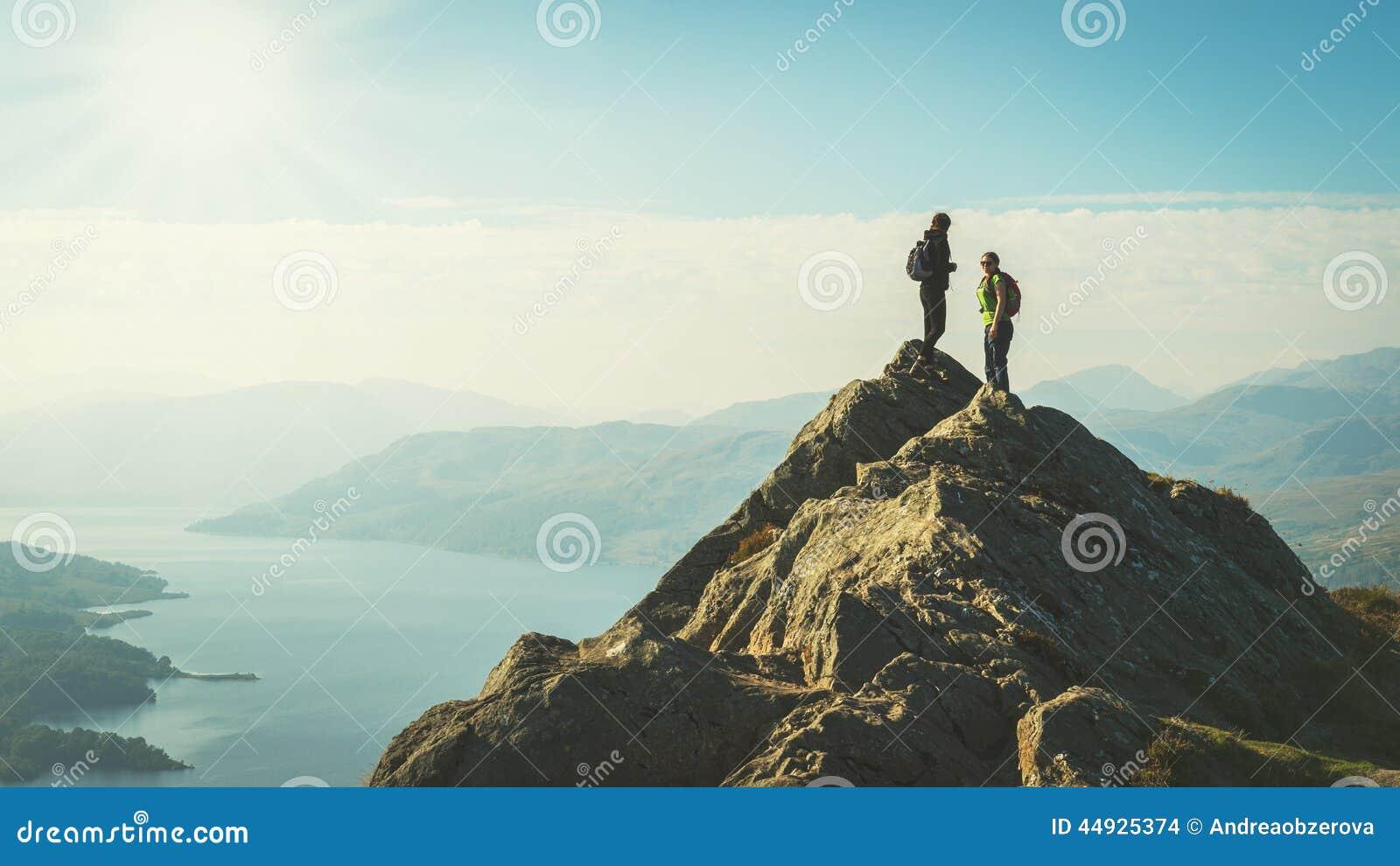 Viandanti femminili sopra la montagna che prende una rottura e che gode di una vista della valle