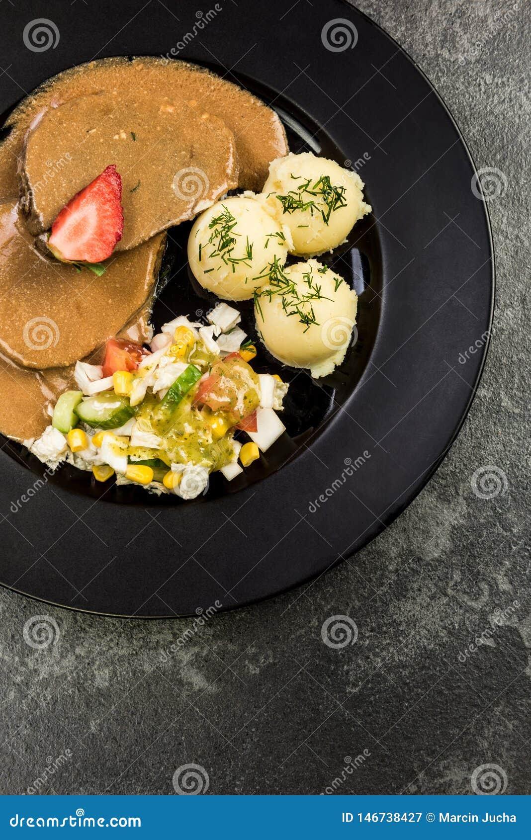 Viande de porc avec de la sauce, les pommes de terre et la salade, partie de portion de restaurant