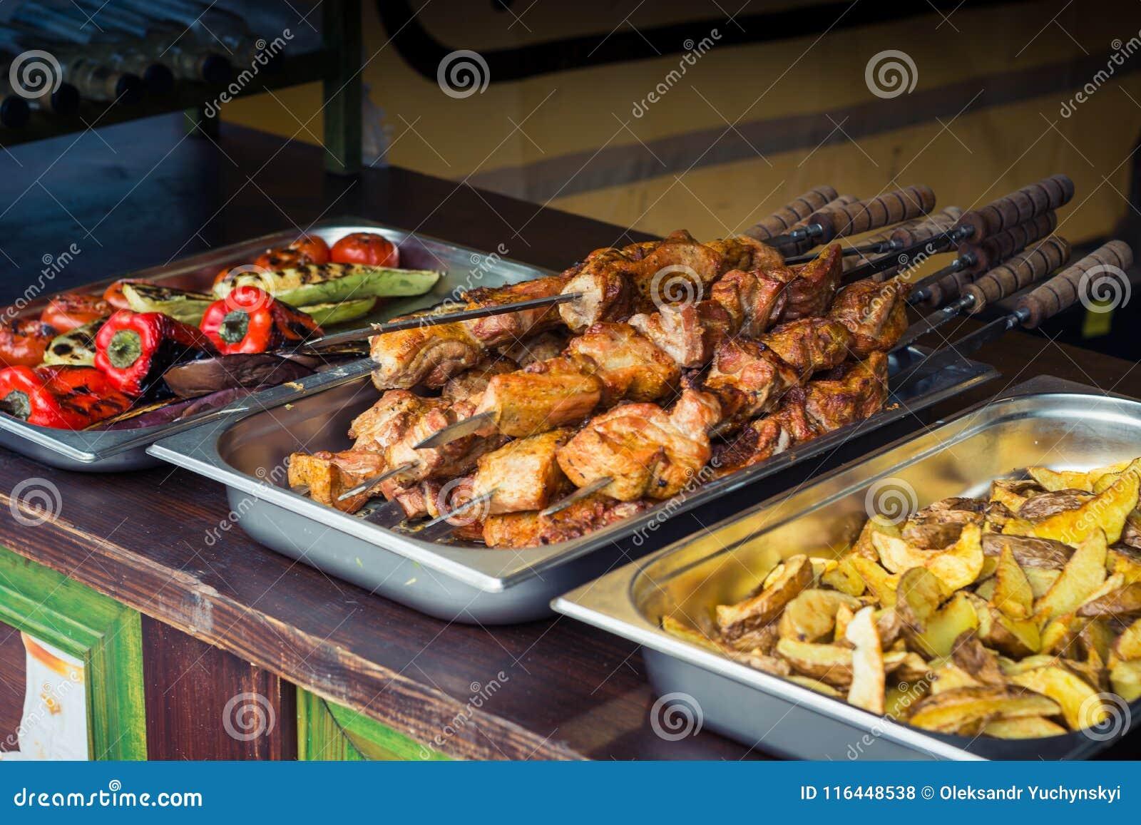 Viande frite sur des brochettes, et légumes grillés sur des plateaux