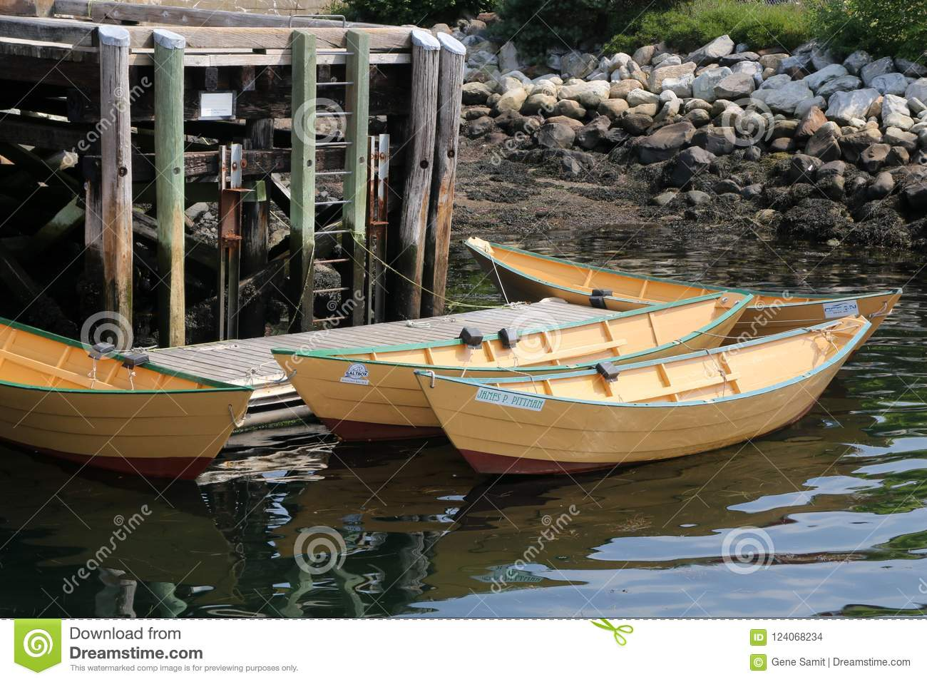 The 3 small rowboats are tied to the pier.